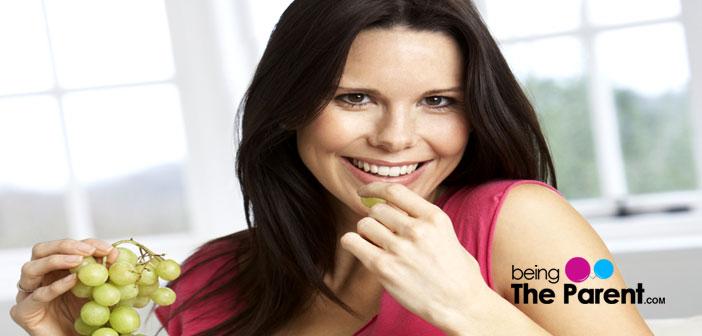 Pregnant woman eating grape