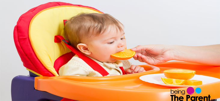 baby eating orange