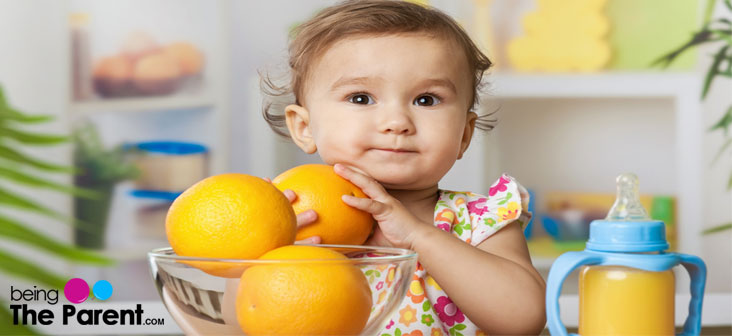 baby with orange and juice