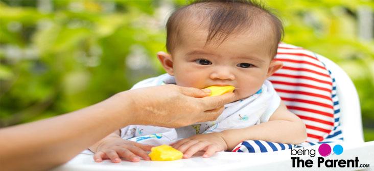 baby eating mango