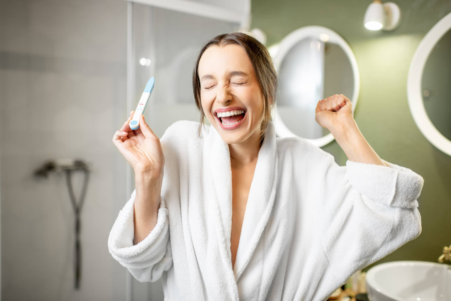 women happy after checking pregnancy result on test kit