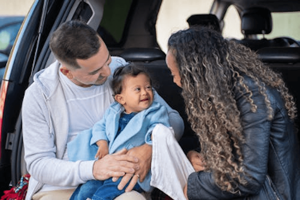 family with baby sitting in back side of a car
