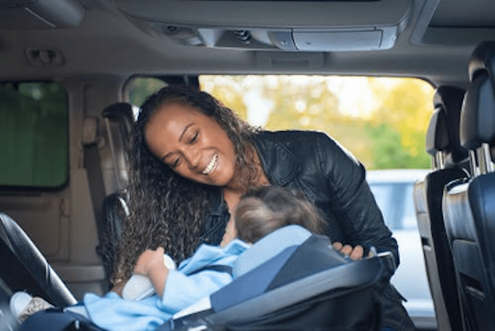 mom and baby in a car seat